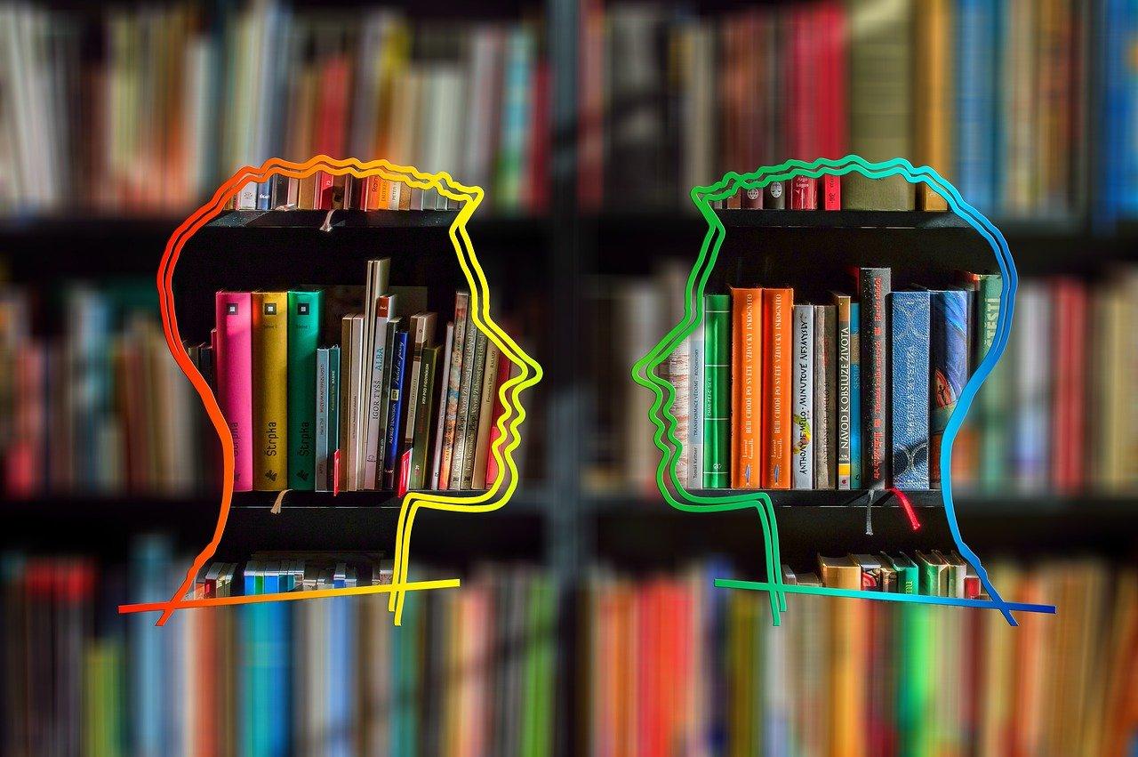 Kuva: kaksi ihmisen pään muotoista silhuettia nenät vastatusten, taustalla kirjahyllyjä